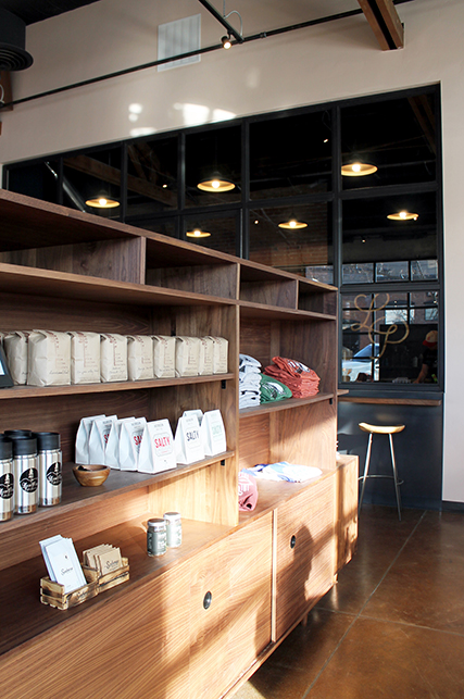 A retail display case made in the mid-century industrial modern style. Bags of coffee and mugs line the shelves