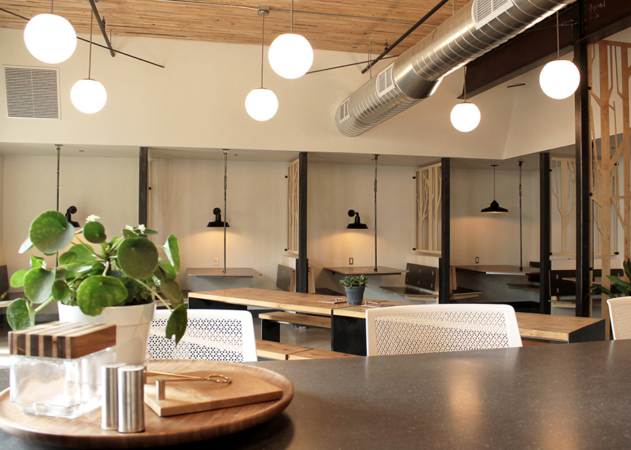 A coffeeshop-like coworking space, private booths line the walls with individual light fixtures and laser-cut wood partitions