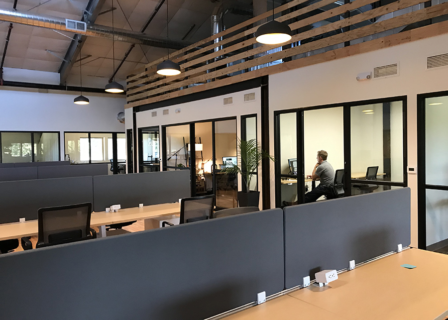 Open co-working stations surrounded by glass-walled private offices exposed ductwork highlights the industrial setting