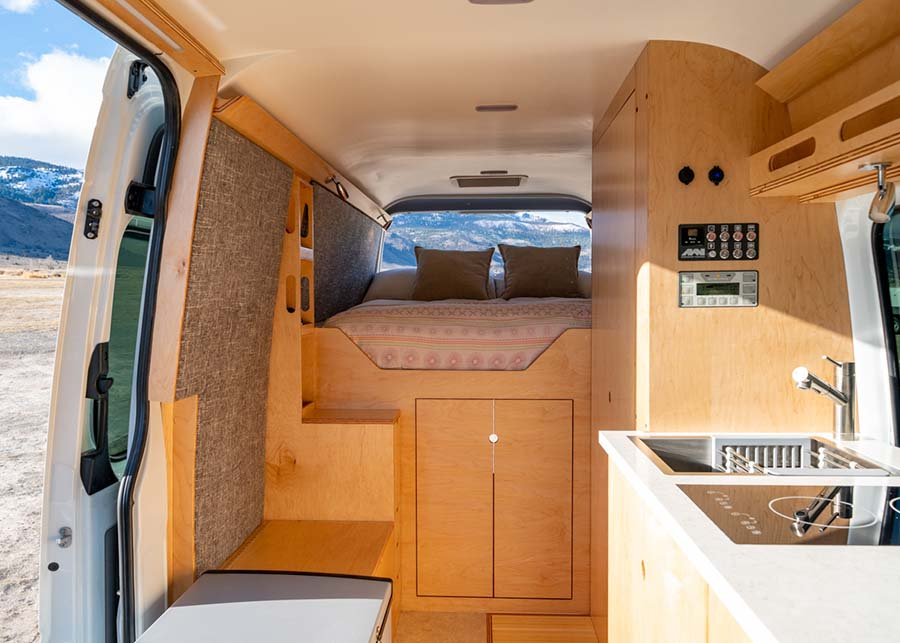 A wide shot of the interior exposed cedar makes the bed frame and storage, a sink and electric stove are the kitchen