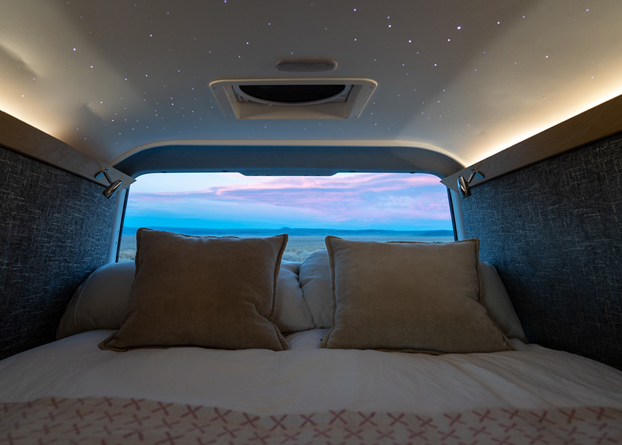 LED lights inlaid on the ceiling create a starry night above the bed; through the back window a pink and blue sunset