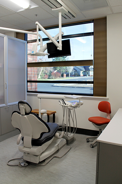 A treatment room set in front of a large window looking out to the neighborhood, a tv hangs from the ceiling