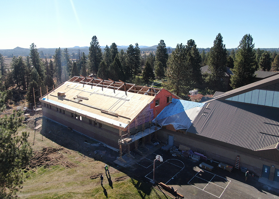 An ariel construction photo - trusses are in place, the roof has been paritially added, the Gym is coming together