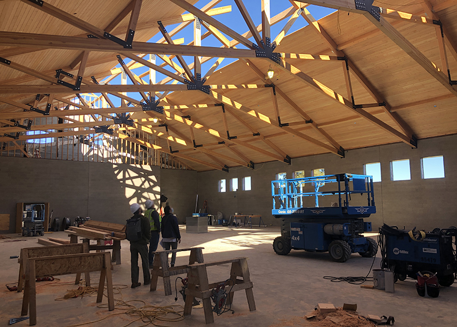 the interior of the Gymnasium. The roof is complete but for a strip along the center that still needs to cedar Nail-lamintated-timber panels that adorn the rest of the ceiling