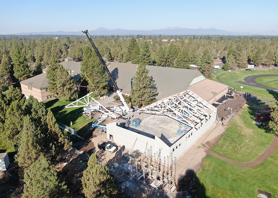 Taken from an ariel view, a crane can be seen lifting one of several trusses into position on the auxillary gym