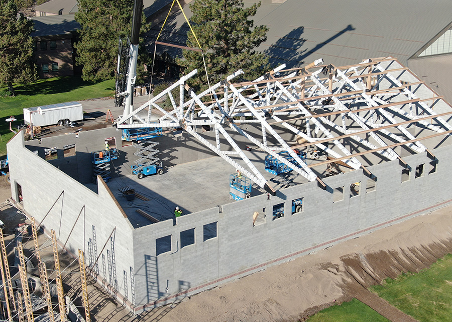 A large crane carefully places one of several a-frame trusses into place with near-impossible accuracy
