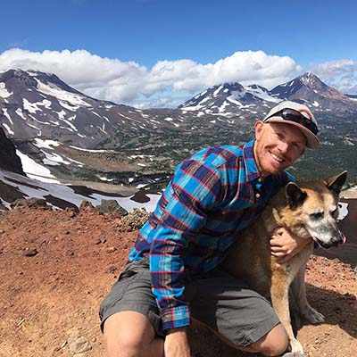 Architect Matt Tynan poses with his dog backed by the cascade mountain range