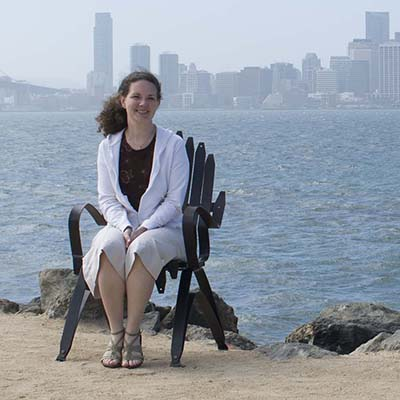 Owner/Architect Rachel Stemach sits on a bench in front of a city skyline